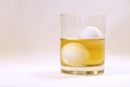 Image of a glass filled with alcohol with golf balls for ice cubes.